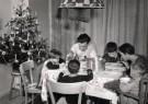 Spaarnestad Fotoarchief,  -  Hongaars zit aan tafel met kerstboom en kerstklok - Postcard -  D1176-1