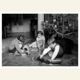 Kerstmis, kinderen spelen onder de kerstbook